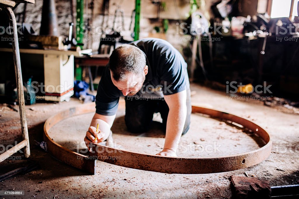 Constructing the metal tyre, Wheelwright, for a wooden cartwheel stock photo