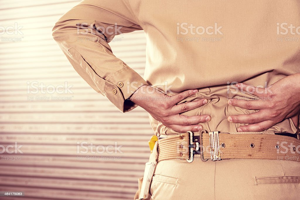Construction: Blue collar worker with back injury. stock photo