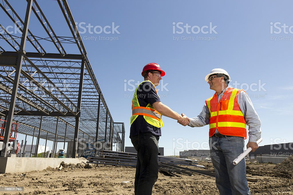 Construction, Blueprints and Handshake royalty-free stock photo