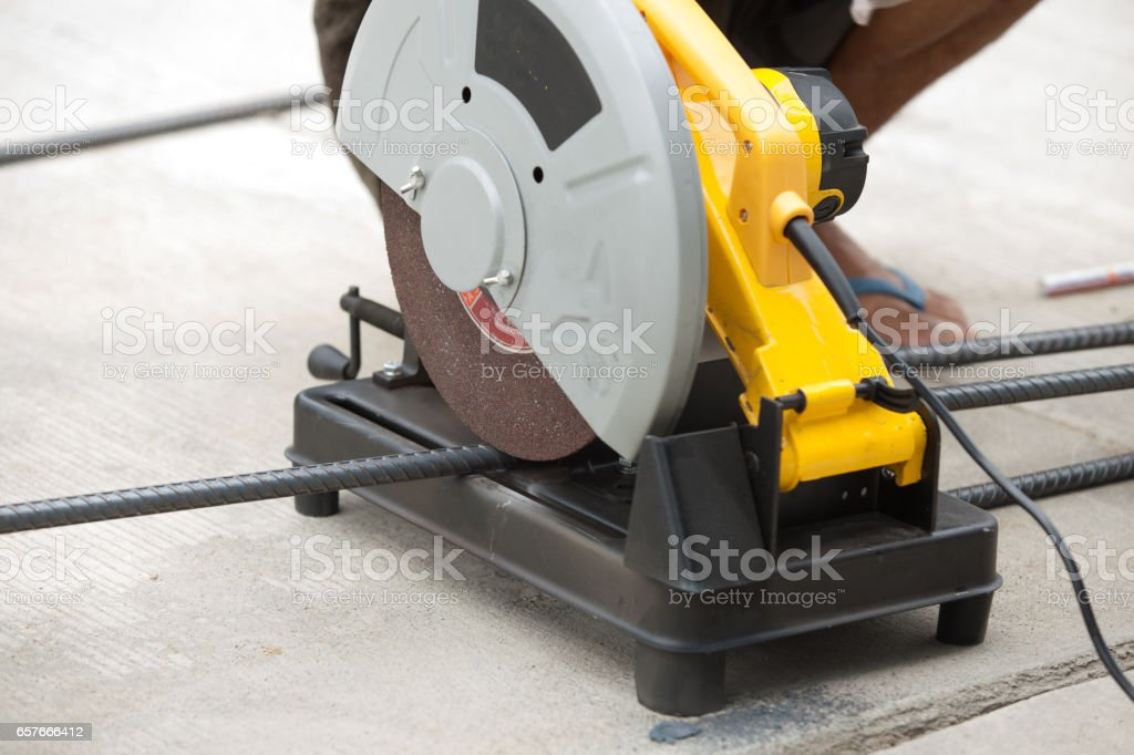Construction builder worker with grinder machine cutting metal reinforcement rebar rods at building site and unsafe stock photo
