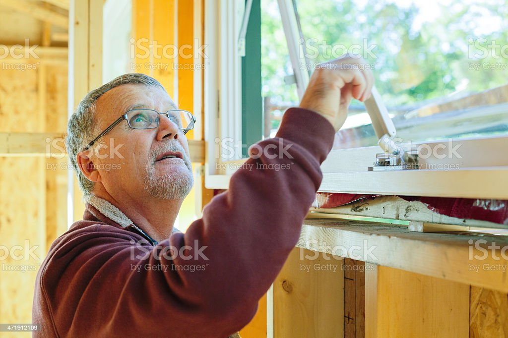 Construction contractor verifying new window installation royalty-free stock photo