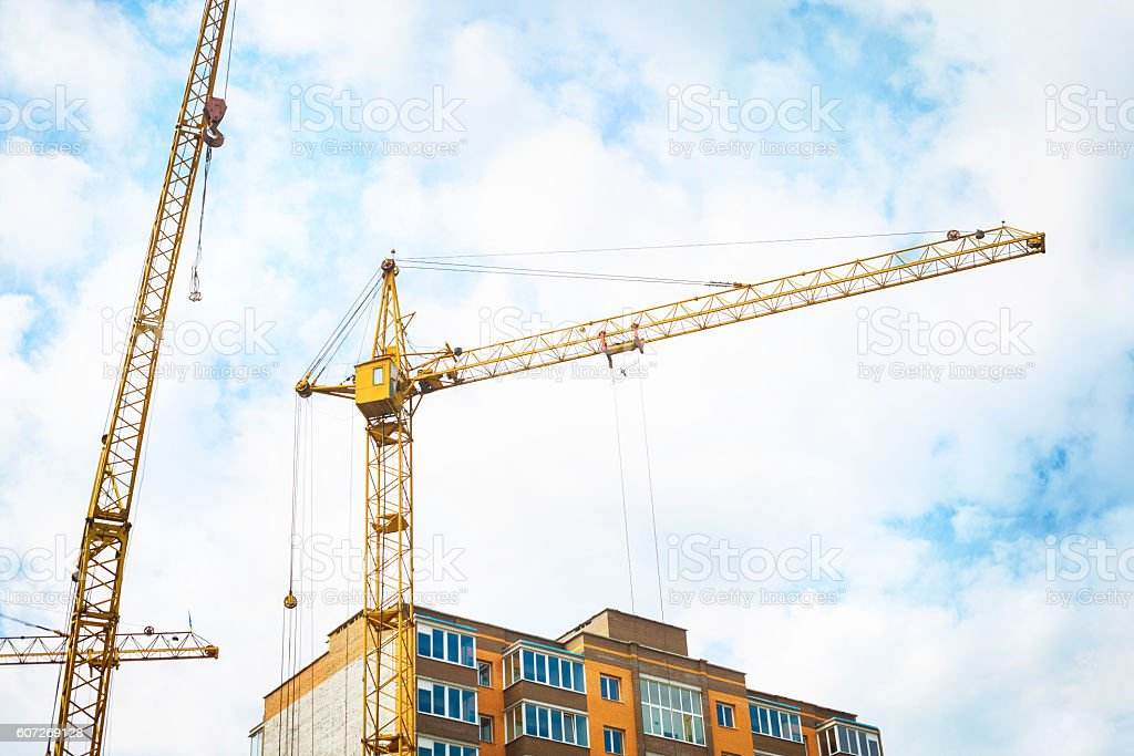 Construction crane and apartment building against. stock photo