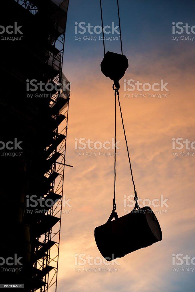 Construction crane holding a barrel stock photo