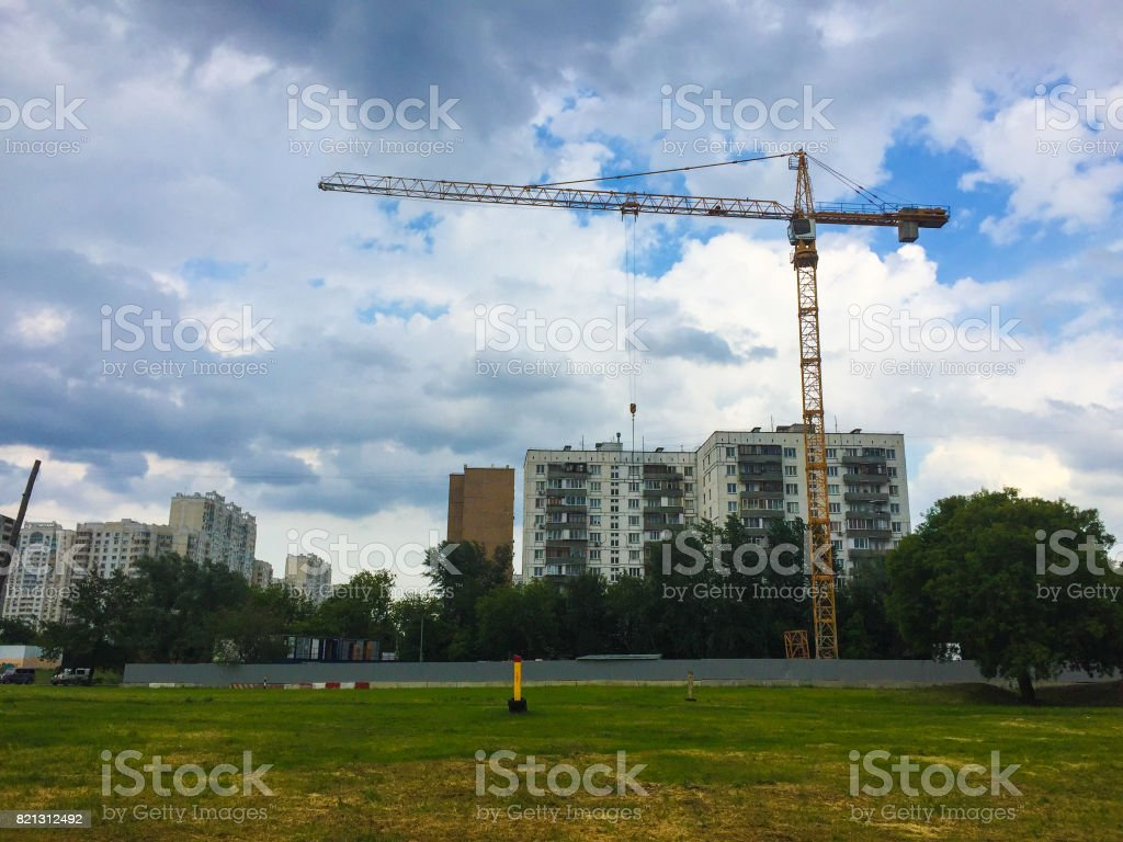 Construction crane on the background of a green grass house stock photo