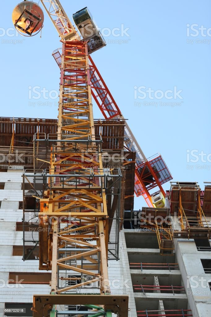 Construction Crane With Cargo In Front Of A Building Under Construction. stock photo