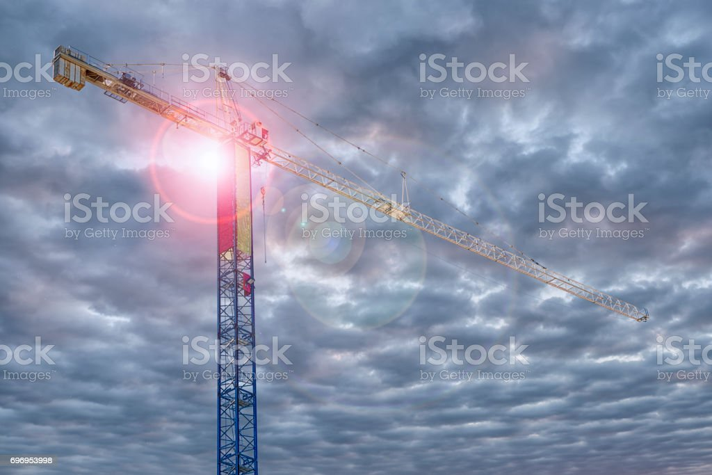 Construction crane with cloudy sky in background. stock photo