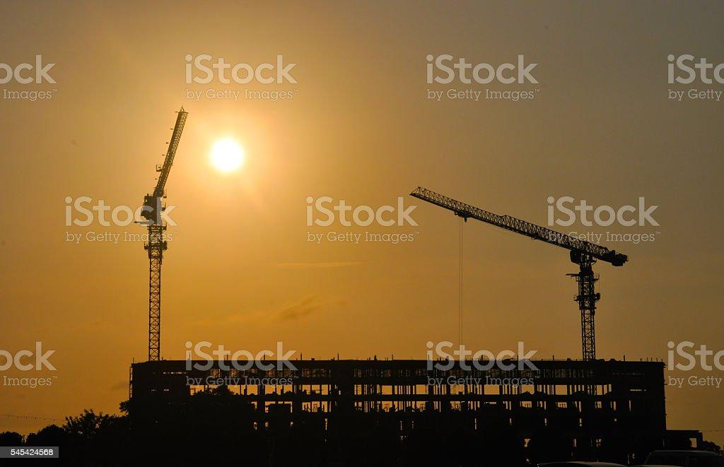 Construction cranes at work against the evening sky foto de stock libre de derechos