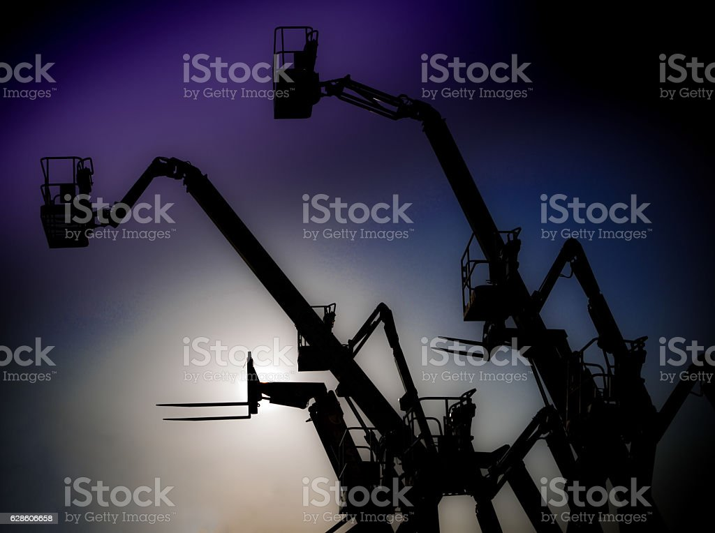 Construction cranes in a silhouetted sky stock photo