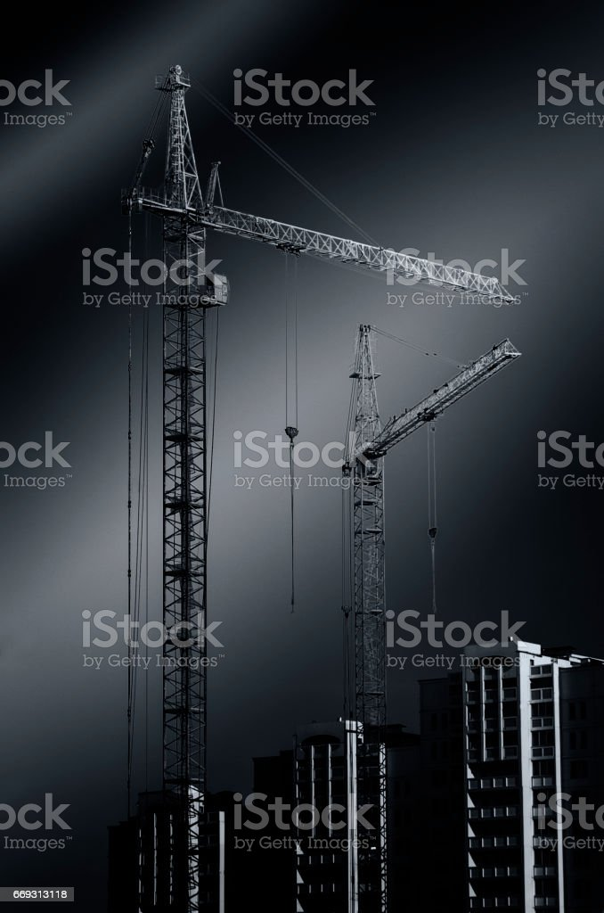 Construction cranes standing on the black background stock photo