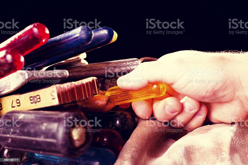 Construction: Electrician removes tools from bag. Screwdriver, pliers. stock photo