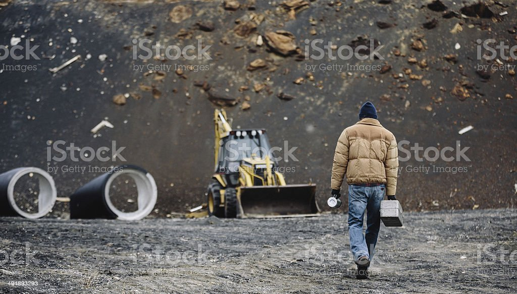Construction Employee walks towards mahinery with lunchbox and coffee stock photo