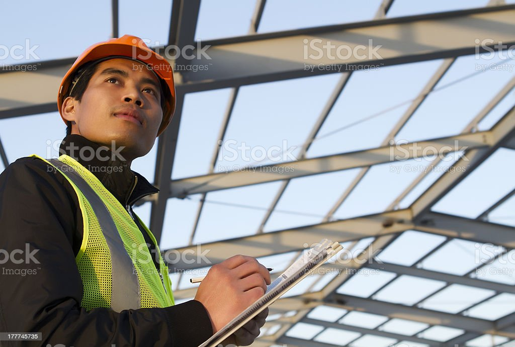 Construction engineer checking plan of new glass building stock photo