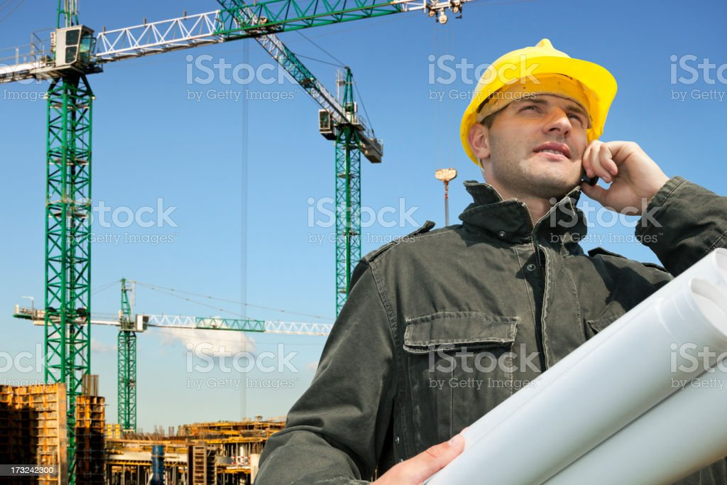 Construction engineer on the construction site talking on the phone. royalty-free stock photo