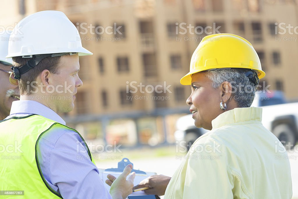 Construction foreman discussing building project with executive royalty-free stock photo