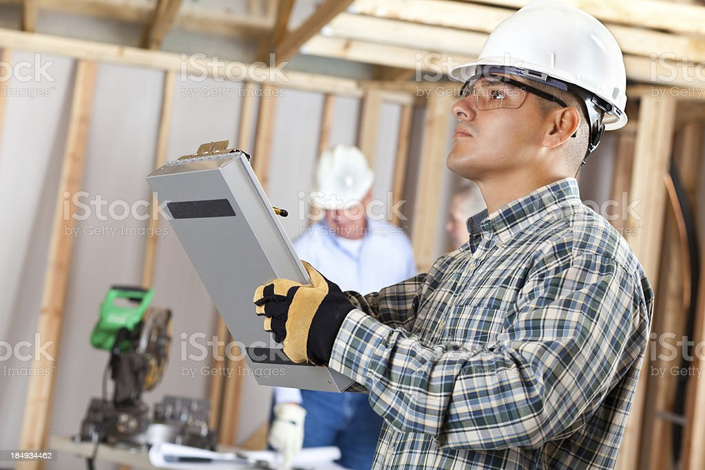 Construction foreman inspecting work at a house building site royalty-free stock photo