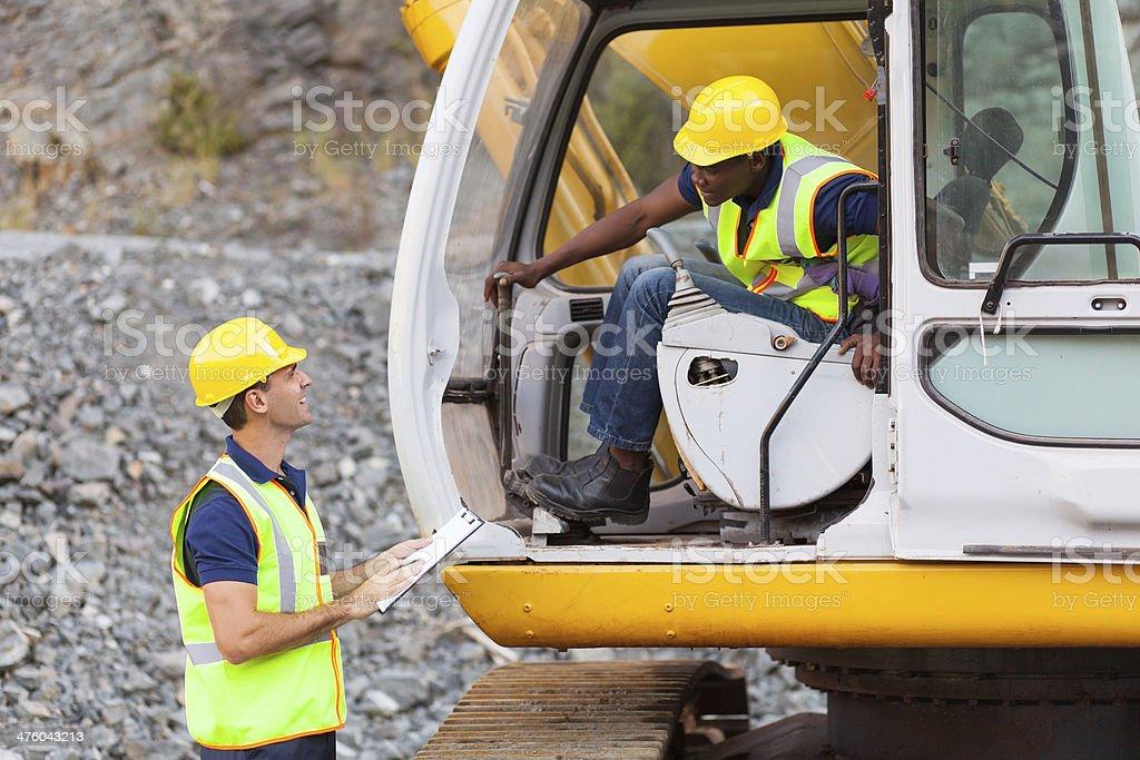 construction foreman talking excavator operator royalty-free stock photo
