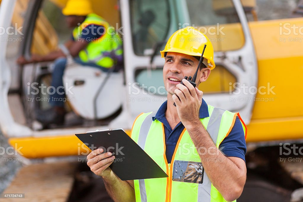 construction foreman talking on walkie-talkie stock photo