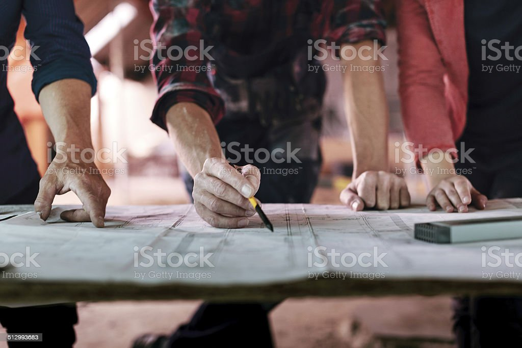 Construction Foreman Writing on Plans stock photo