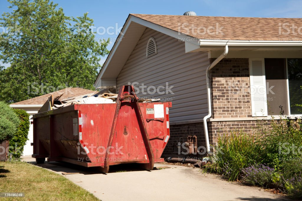Construction garbage container next to house stock photo