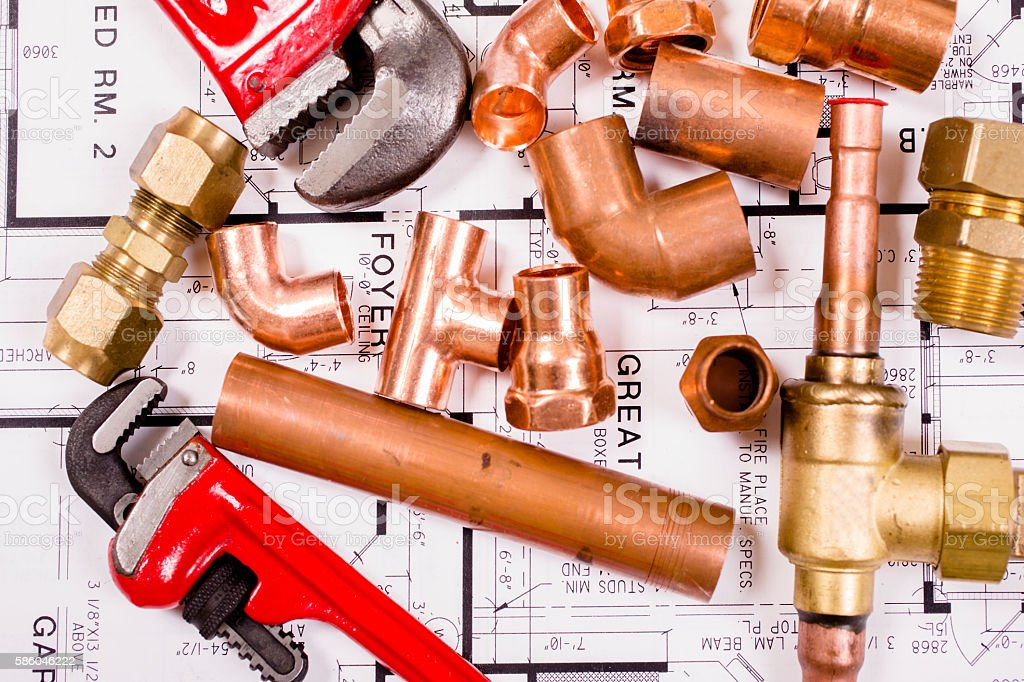 Construction hand tools, plumbing pipes on house plans. stock photo