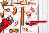 Construction hand tools, plumbing pipes on house plans.