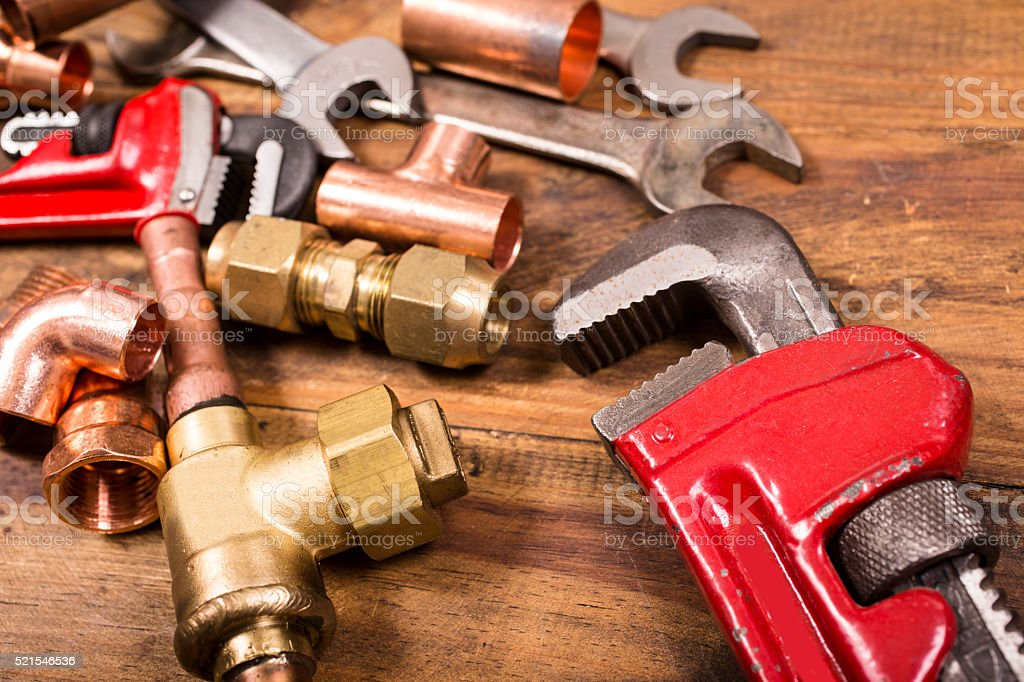 Construction hand tools, plumbing pipes on rustic wooden table. stock photo
