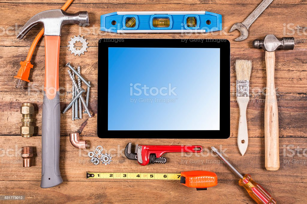 Construction hand tools surround a digital tablet. stock photo