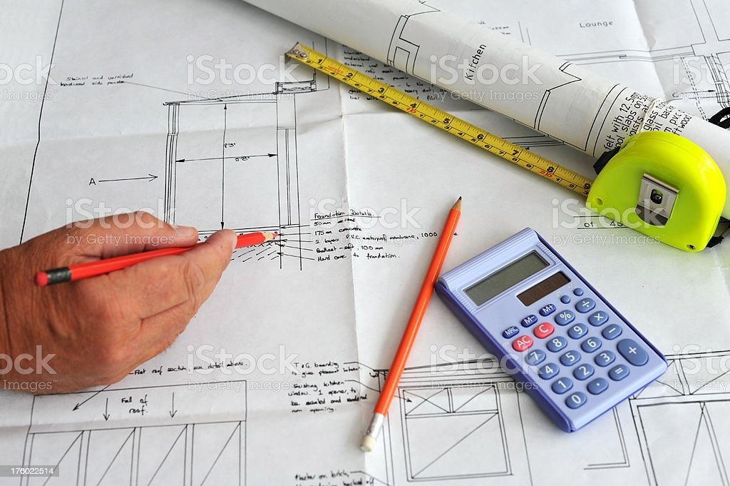 Construction house extension building plans with hand holding a pencil royalty-free stock photo