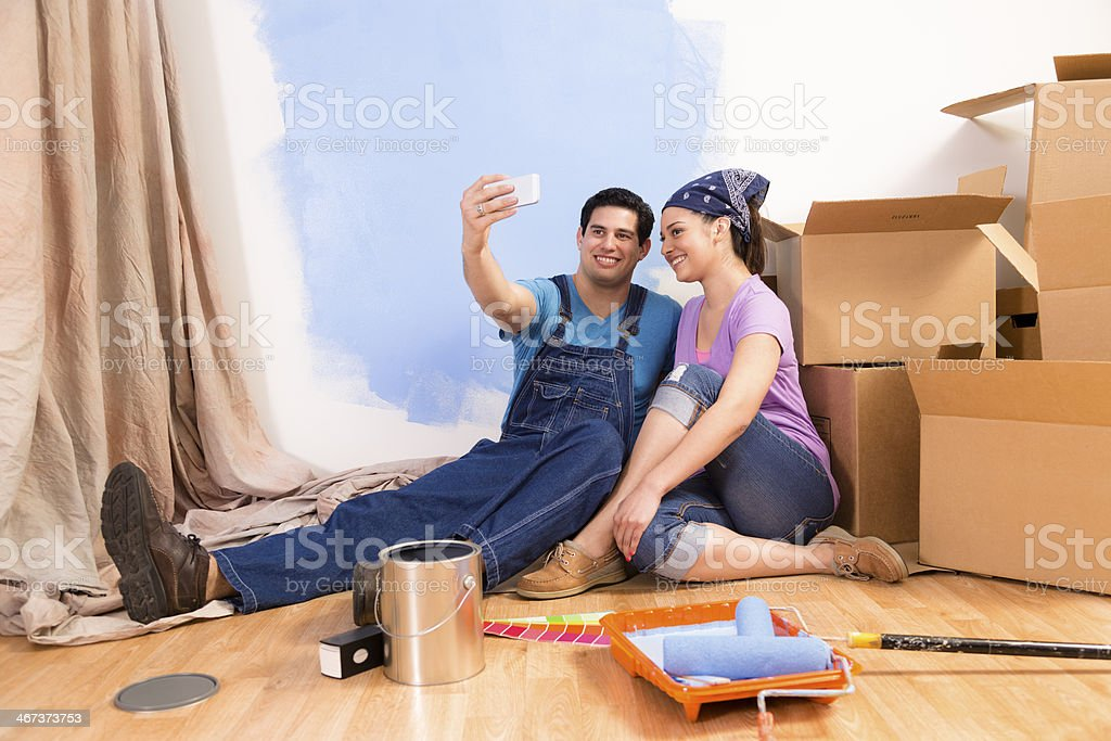 Construction: Latin couple. Home improvement, moving. Taking 'selfie.' royalty-free stock photo