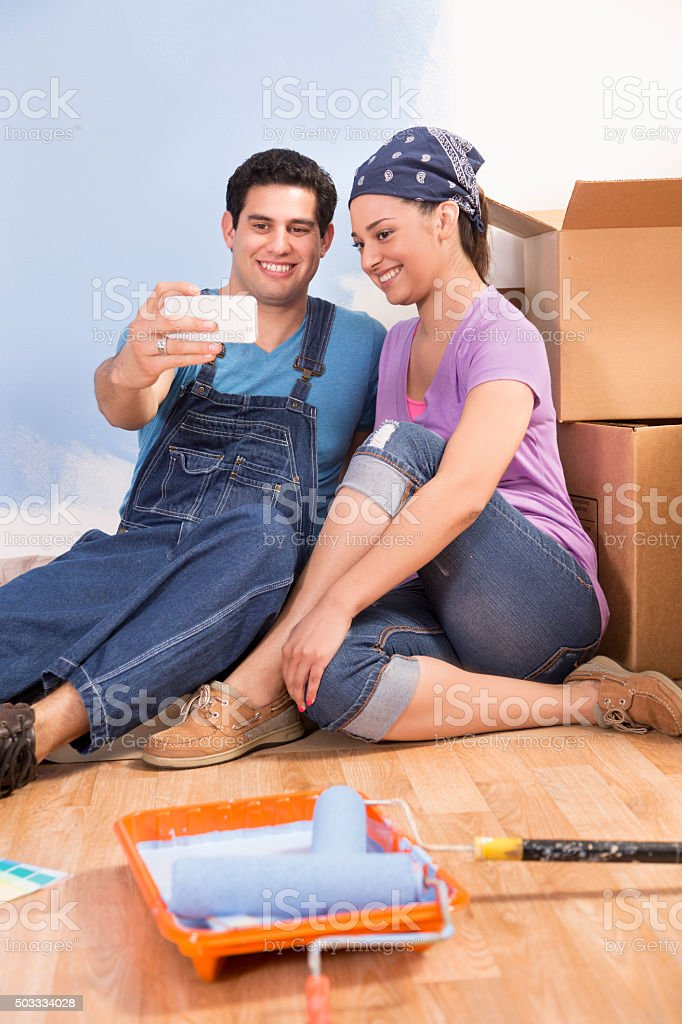 Construction: Latin couple. Home improvement, moving. Taking 'selfie.' stock photo