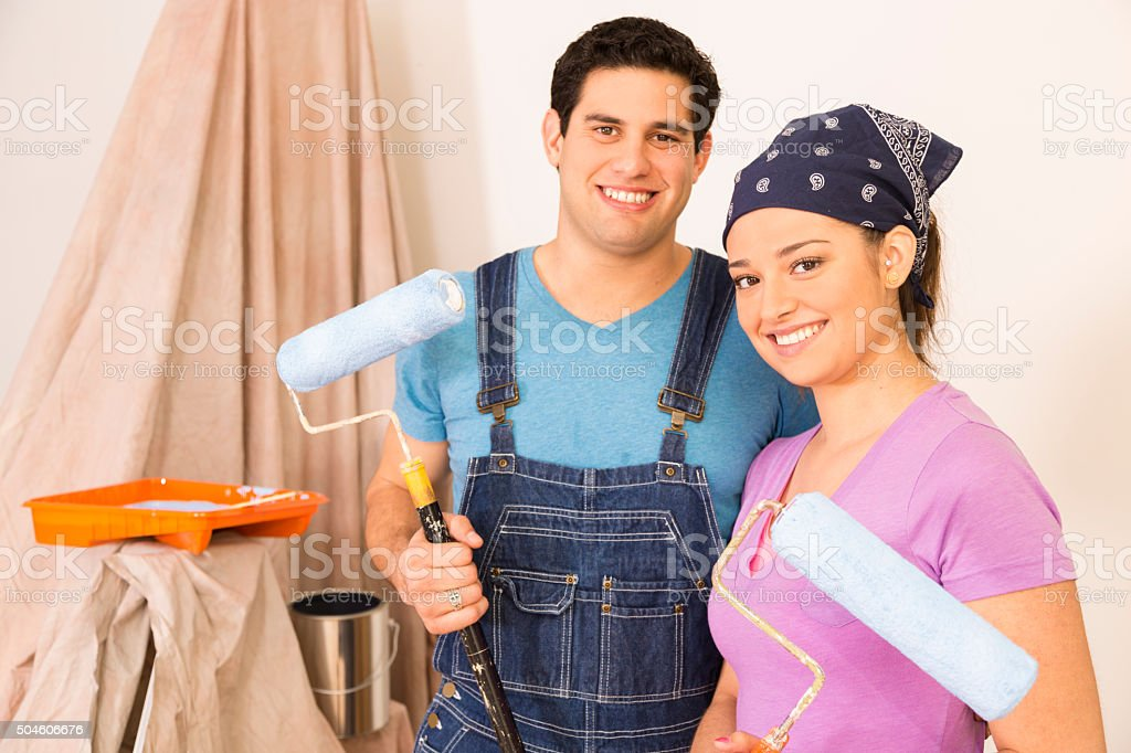 Construction: Latin couple remodeling their home. Painting. stock photo