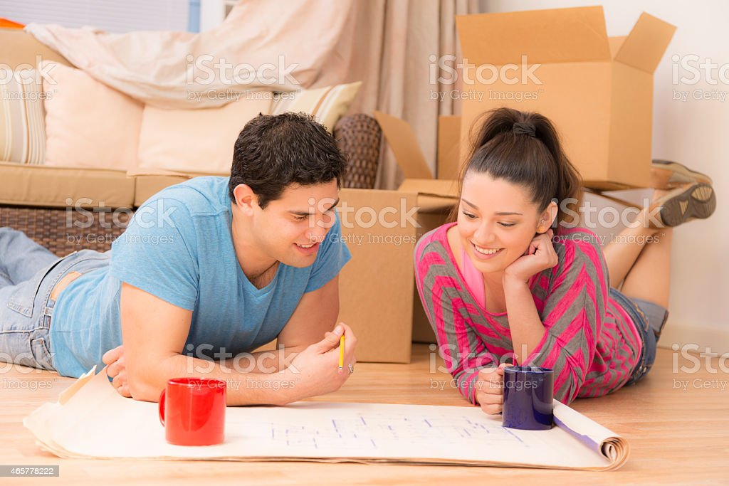 Construction: Latin couple views floorplans for new home. Moving boxes. stock photo
