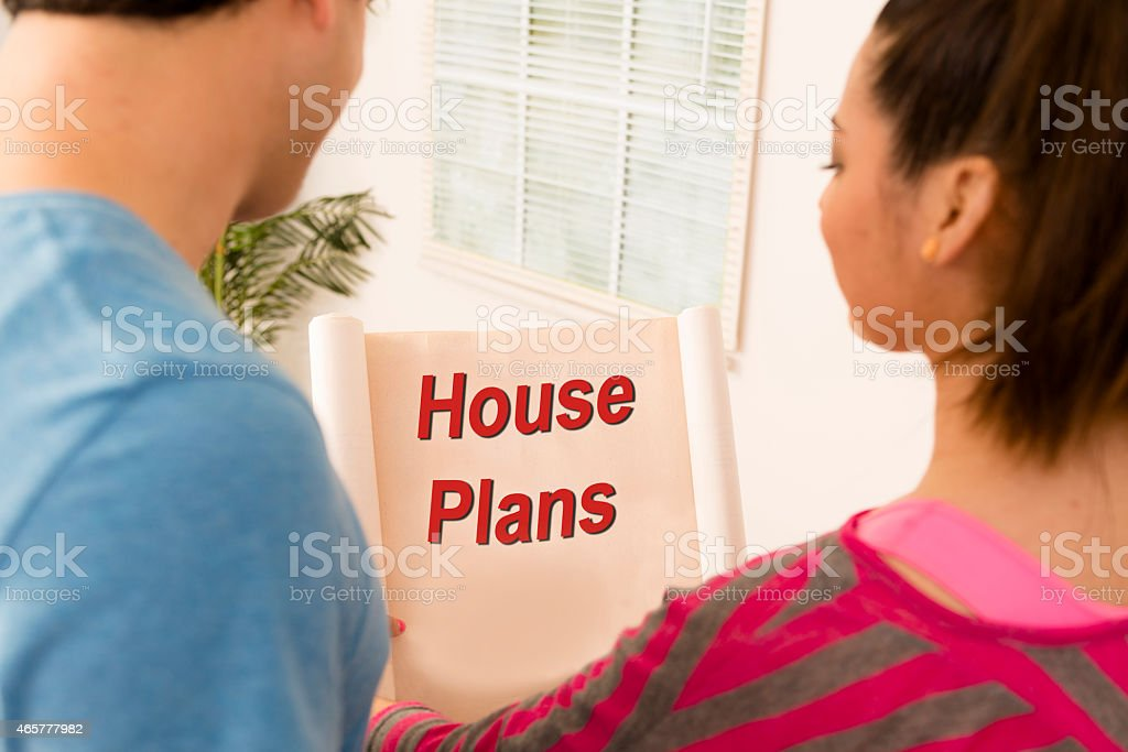 Construction: Latin couple views floorplans for new home or addition. stock photo