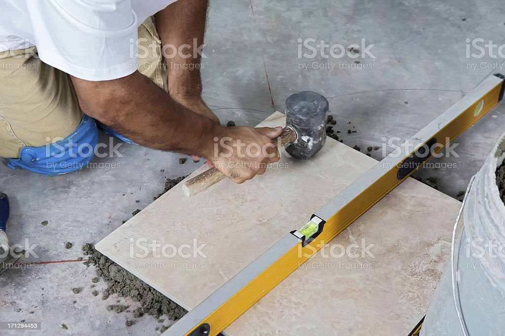 Construction: Laying a Porcelain Floor with levels stock photo