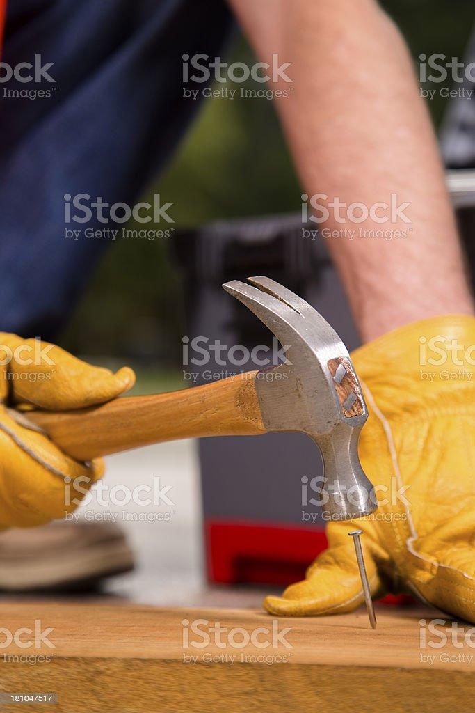 Construction:  Man hammering nail into lumber. Remodel job royalty-free stock photo