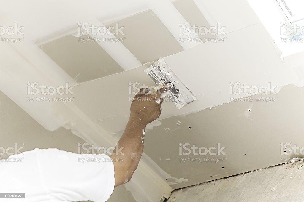 Construction: Man installing plasterboard stock photo