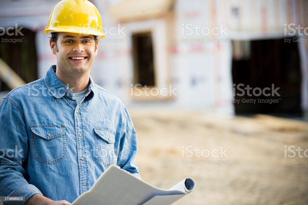 Construction man wearing a hard hat and holding blueprints royalty-free stock photo