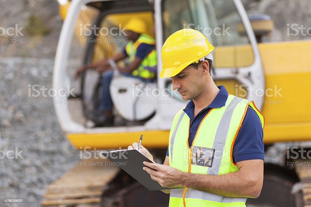 construction manager writing report stock photo