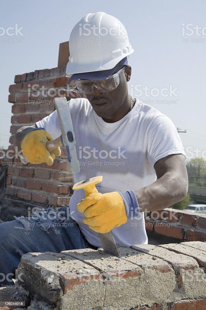 Construction mason removes mortar from brick joint. royalty-free stock photo