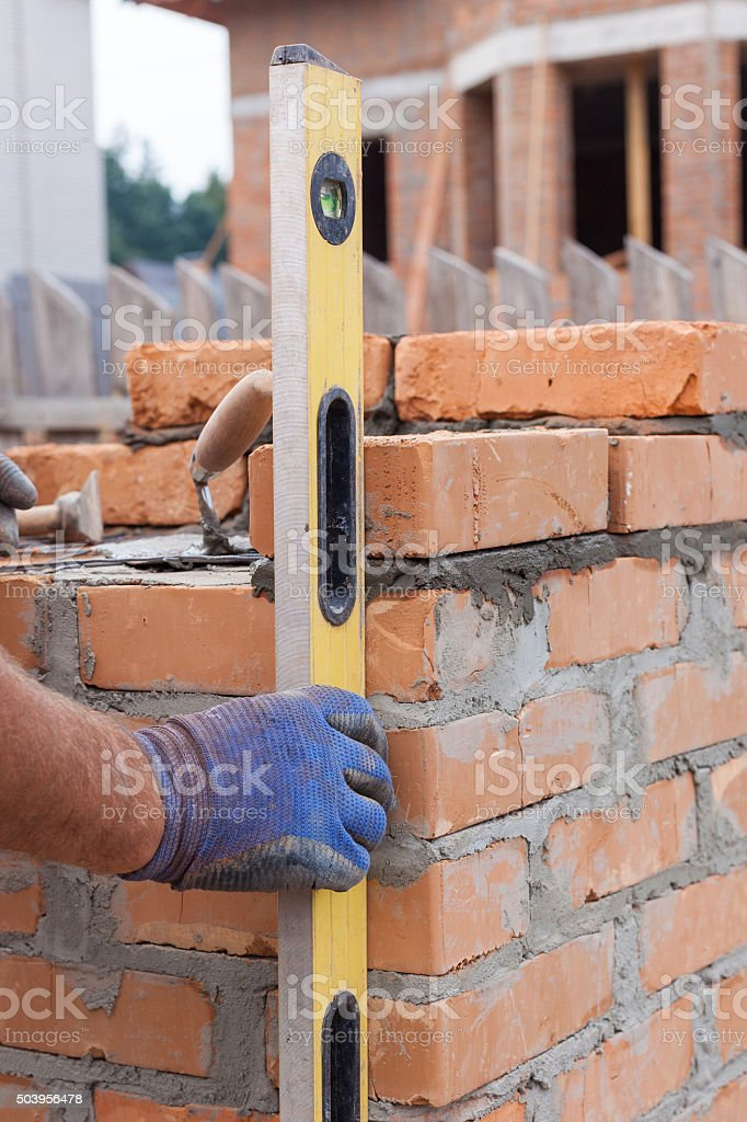 Construction mason worker measuring with professional level the bricks stock photo