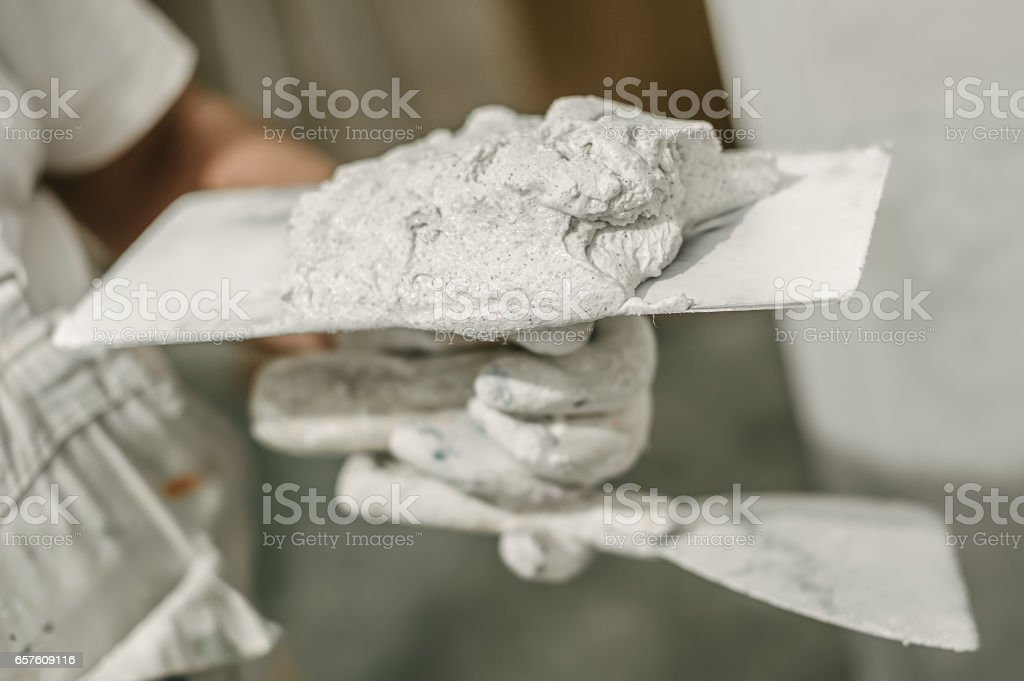 Construction mason worker with spatula and mortar stock photo