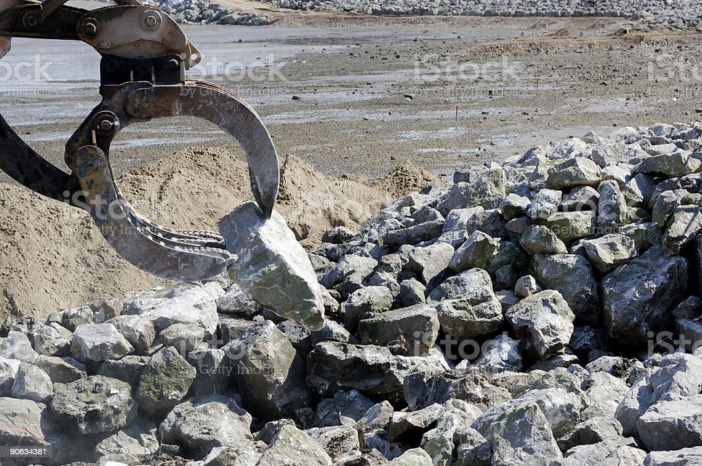 Construction mechanical jaw moving rock, restoring sea wall royalty-free stock photo