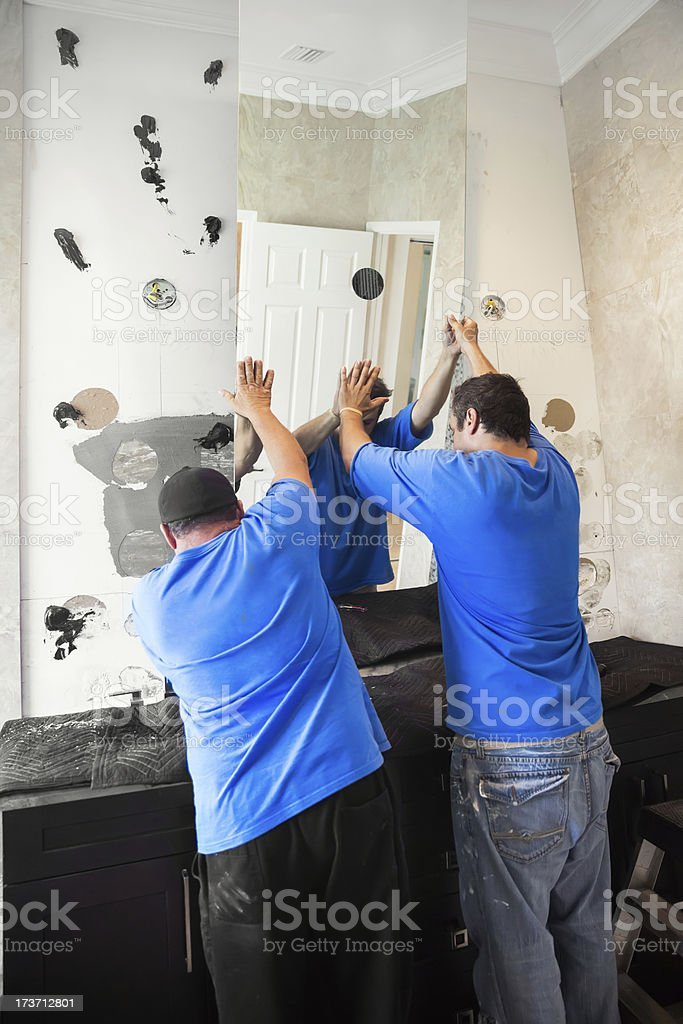 Construction: Men installing a large mirror series royalty-free stock photo
