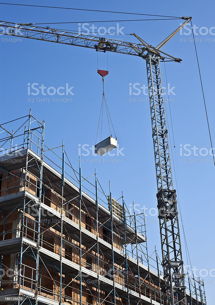 Construction Of Building With Crane Against Blue Sky stock photo