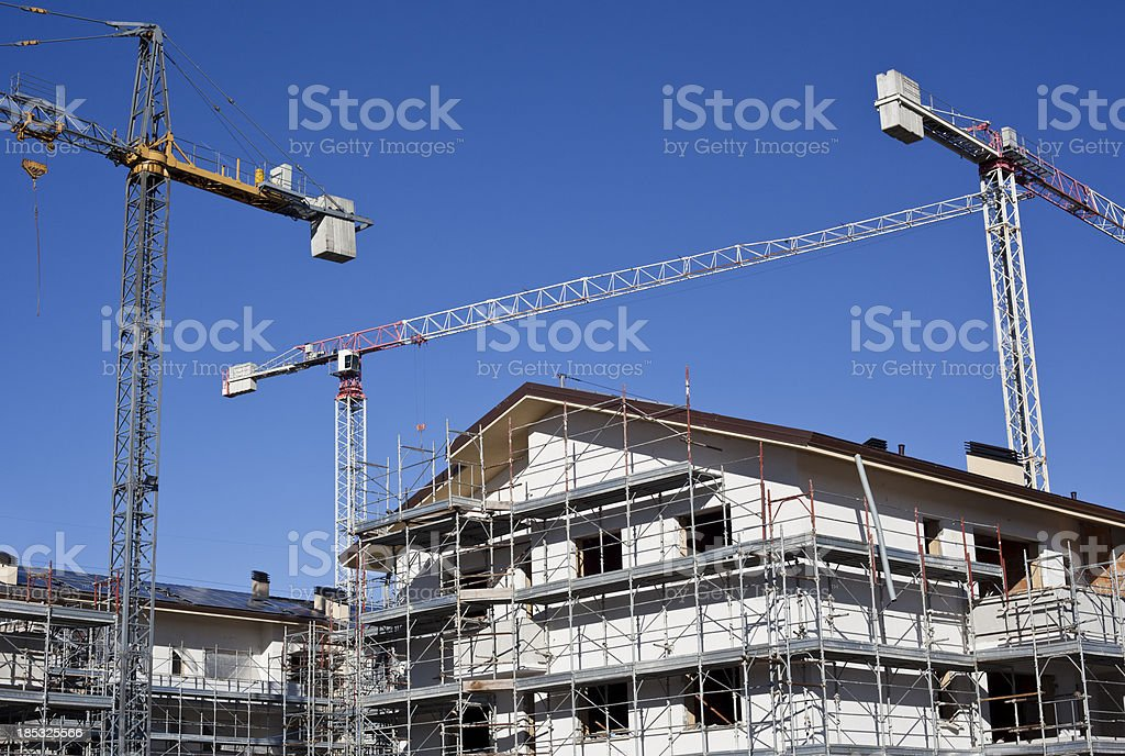 Construction Of Building With Cranes Against Blue Sky stock photo