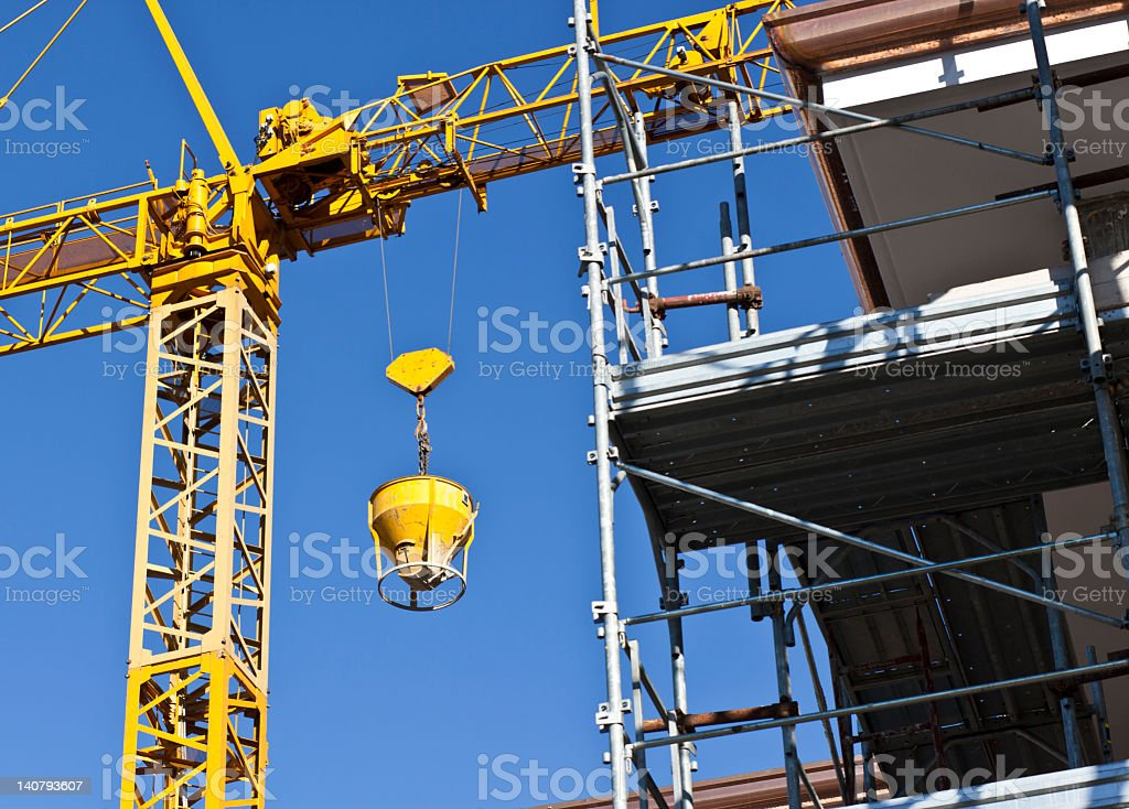 Construction Of Building With Yellow Crane Against Blue Sky stock photo