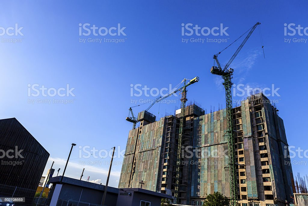 construction of high-rise buding by tower cranes and the canvas stock photo