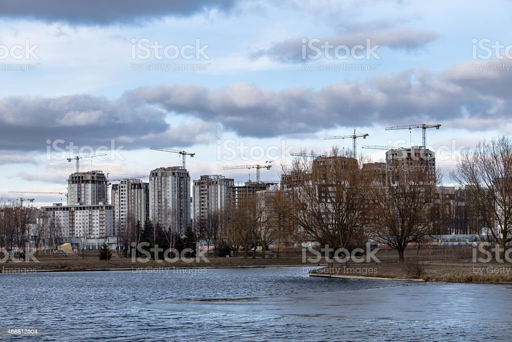 Construction of high-rise buildings with cranes on river bank stock photo