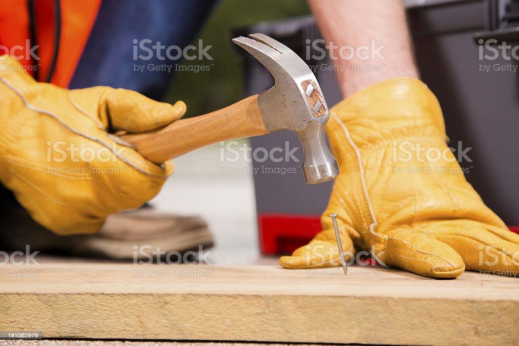 Construction:  Person hammering nail into 2x4. Repairman job work. royalty-free stock photo