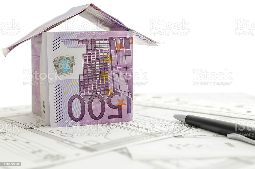 Construction plan with house made of money on it royalty-free stock photo